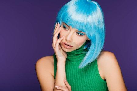Photo pour À la mode jeune femme posant dans perruque bleu, isolé sur violet - image libre de droit