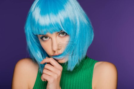 beautiful girl posing in trendy blue wig, isolated on purple