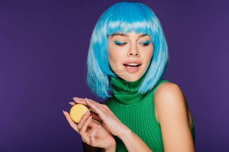 Photo for Stylish sensual girl in blue wig posing with macaron isolated on purple - Royalty Free Image