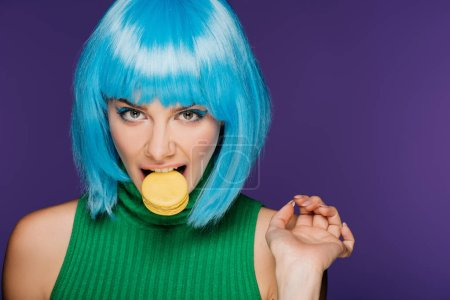 attractive sensual woman in blue wig biting macaron isolated on purple