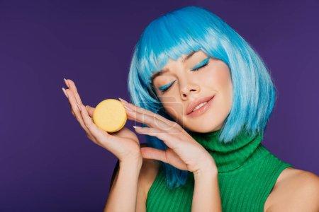 Photo pour Fille rêveuse dans perruque bleu posant avec macaron isolé sur violet - image libre de droit