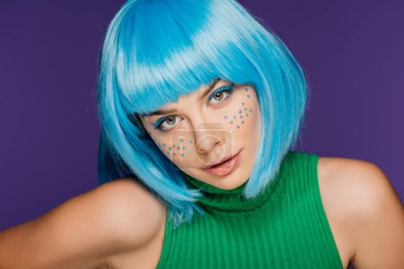 attractive glamor girl with blue wig and stars on face, isolated on purple