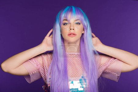 pretty fashionable girl posing in violet wig with stars on face, isolated on purple
