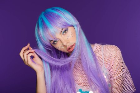 beautiful charming girl posing in violet wig with stars on face, isolated on purple