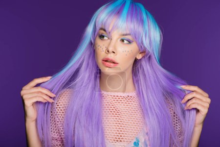 attractive pretty girl posing in violet wig with stars on face, isolated on purple