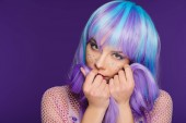 beautiful stylish young woman posing in violet wig with stars on face, isolated on purple