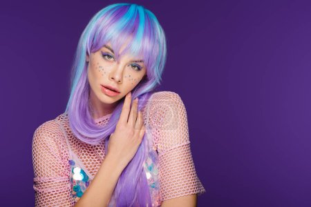 beautiful fashionable woman posing in violet wig with stars on face, isolated on purple