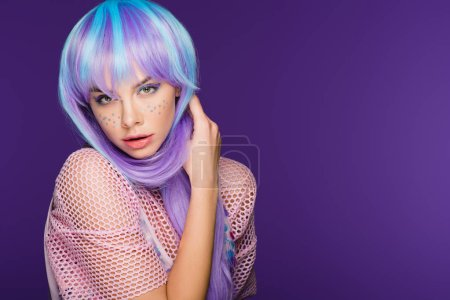 attractive fashionable girl posing in violet wig with stars on face, isolated on purple