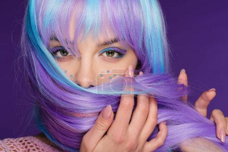 beautiful stylish girl posing in violet wig with stars on face, isolated on purple