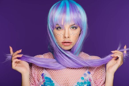 beautiful young woman posing in violet wig with stars on face, isolated on purple