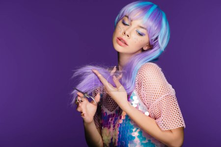 fashionable girl with stars on face cutting violet hair with scissors, isolated on purple