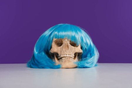 skull in blue wig on table with purple background