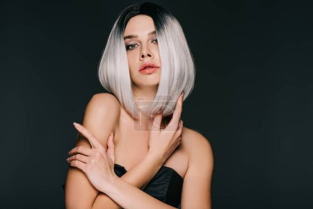 beautiful fashionable young woman posing in grey wig, isolated on black