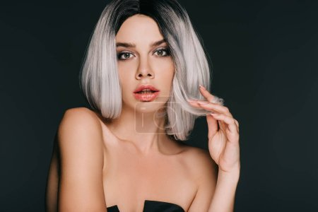 attractive model posing in grey wig for fashion shoot, isolated on black
