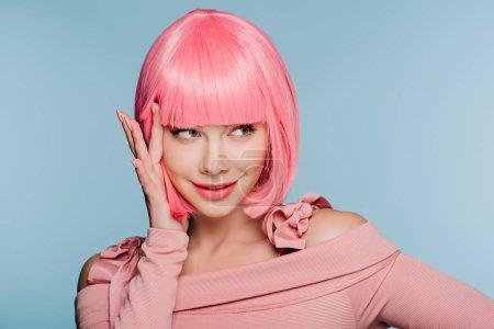 Foto de Chica moda feliz gesticular y posando en rosa peluca aislada en azul - Imagen libre de derechos