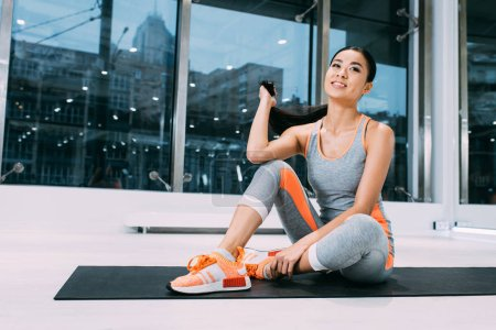 Photo for Attractive asian sportswoman sitting on fitness mat and holding hair at modern gym - Royalty Free Image