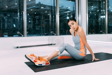 Photo for Beautiful asian sportswoman sitting on fitness mat and looking at camera at gym - Royalty Free Image