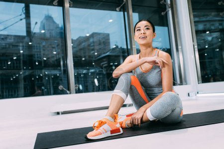 Photo for Attractive asian sportswoman sitting on mat and smiling at gym - Royalty Free Image