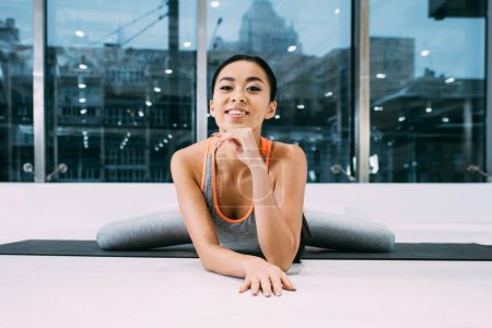 close up view of smiling asian girl doing split and looking at camera on fitness mat at gym