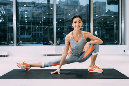 flexible asian girl smiling and stretching leg on fitness mat in health club