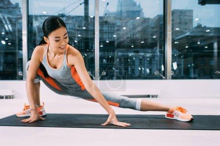 Photo pour Flexible asiatique fille sourire et étirement jambe sur fitness mat à la salle de gym - image libre de droit
