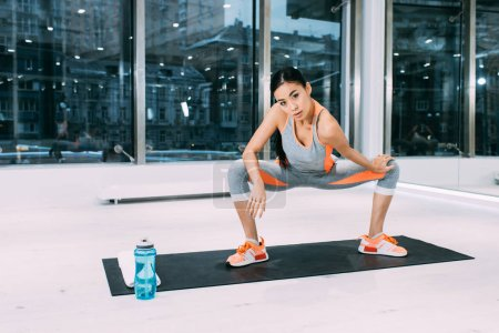 athletic asian sportswoman doing fitness exercise on mat and looking at camera at gym