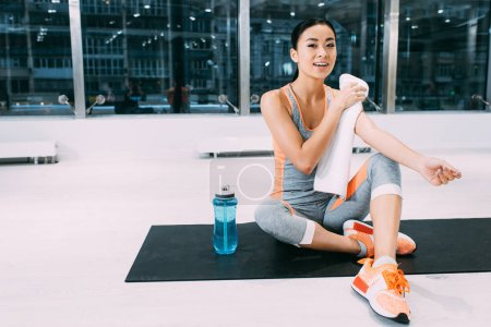 smiling asian girl sitting on fitness mat and wiping shoulders with towel at modern gym