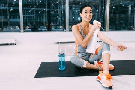 Photo pour Sourire asiatique fille assis sur tapis de fitness et essuyer les épaules avec serviette à la salle de gym moderne - image libre de droit