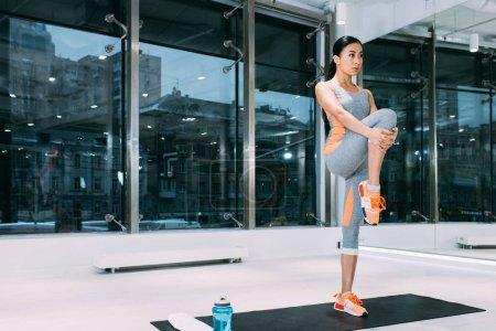 Photo pour Fille asiatique mince debout sur le tapis fitness et en étirant la jambe au gymnase moderne - image libre de droit