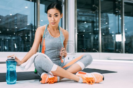 attractive asian girl with skipping rope on shoulders sitting on fitness mat, touching sports bottle with water and looking at camera at gym