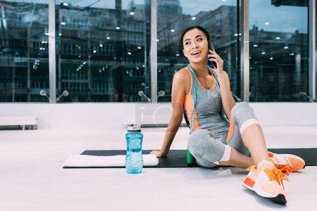 Photo pour Attrayant asiatique sportive assis sur tapis de fitness et parler sur smartphone dans le centre sportif - image libre de droit