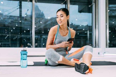 Photo pour Souriant asiatique sportive assis sur tapis de fitness et tenant smartphone dans le centre sportif - image libre de droit