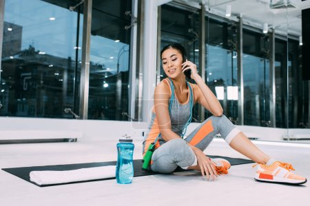 beautiful asian sportswoman sitting on fitness mat and talking on smartphone at gym