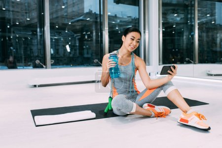 smiling asian sportswoman sitting on fitness mat, holding sports bottle with water and taking selfie at gym
