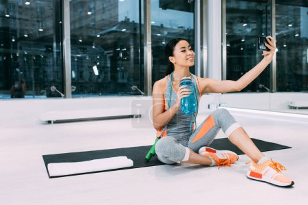smiling asian girl sitting on fitness mat, holding sports bottle with water and taking selfie at gym