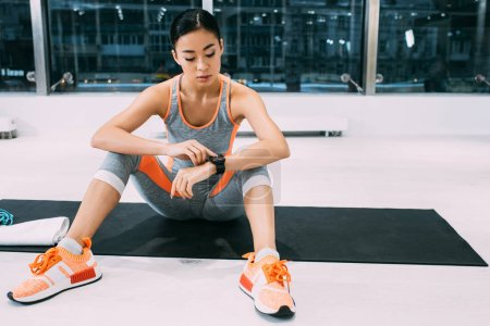 attractive asian sportswoman sitting on mat and looking at fitness tracker at gym