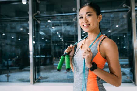 smiling asian sportswoman holding skipping rope on shoulders at gym