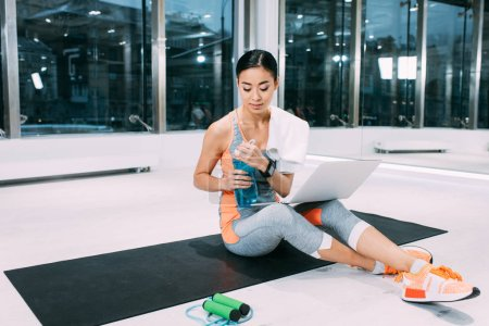 Photo for Asian sportswoman sitting with laptop on fitness mat and holding sports bottle at gym - Royalty Free Image