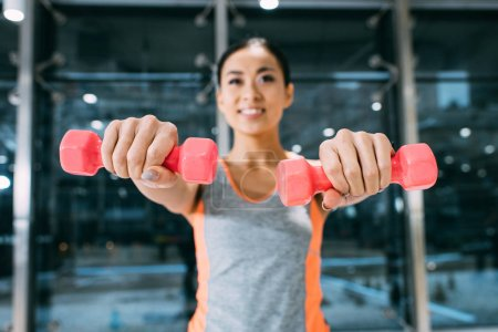 Photo for Close up view of smiling asian sportswoman doing exercise with dumbbells at gym - Royalty Free Image