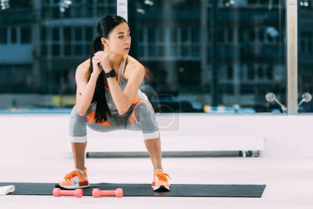 Photo for Attractive asian girl doing squats on fitness mat at gym - Royalty Free Image