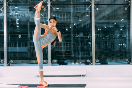 athletic asian girl in sportswear with leg up standing on fitness mat at gym