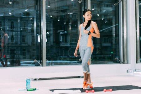 Photo pour Mince asiatique fille debout sur fitness mat et toucher les cheveux dans le centre sportif - image libre de droit