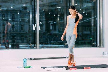 Photo pour Belle sportive asiatique toucher les cheveux et debout sur le tapis de fitness au centre sportif - image libre de droit