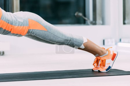 Photo for Cropped view of sportswoman exercising on fitness mat at gym - Royalty Free Image