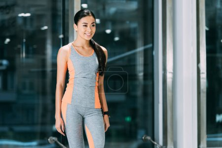 slim asian girl in sportswear smiling at gym
