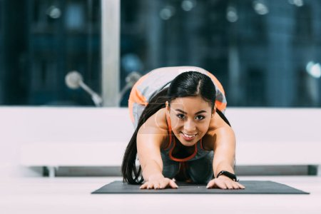 attractive asian sportswoman doing stretch exercises on fitness mat and smiling at gym