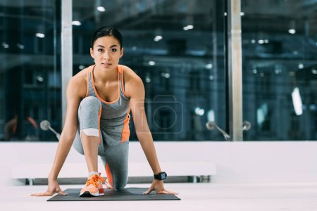 athletic asian sportswoman stretching on fitness mat in sports center
