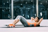 beautiful asian sportswoman doing sit-ups on fitness mat in sports center