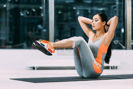 slim asian sportswoman exercising on fitness mat in sports center