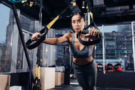 Photo for Slim asian sportswoman training with resistance bands at gym - Royalty Free Image